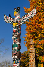 Kakasolas And Beaver Crest Totem Poles In Stanley Park Vancouver With Raven On Blue Sky And Fall Leaves