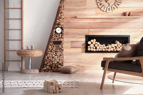 Fotografía Decorative fireplace with stacked wood in cozy living room interior
