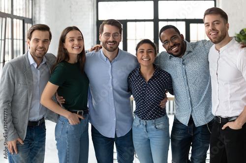 Obraz na plátně Smiling diverse business people, successful team, staff members hugging, standin