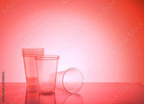Obraz empty disposable plastic cups on a red background with copy space - fototapety do salonu