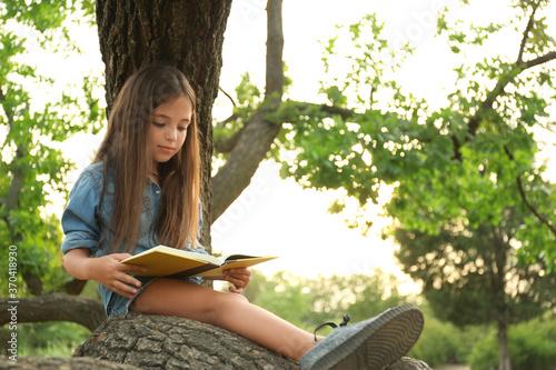 Obraz Cute little girl reading book on tree in park - fototapety do salonu