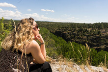 Thoughtful Blonde Girl Looking At The Horizon With Sunglasses And With A Leafy Background Of Trees