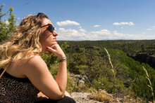 Thoughtful Blonde Girl Looking To The Horizon With A Leafy Background Of Trees
