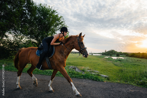 A young pretty girl jockey riding a thoroughbred stallion is engaged in horse riding at sunset Canvas-taulu
