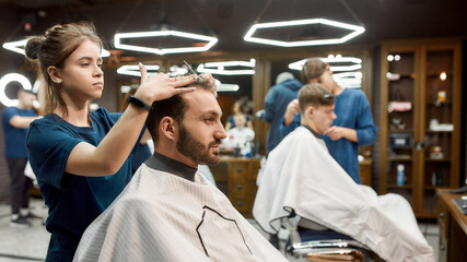 Man visiting barbershop. Side view of a professional barber girl making new modern haircut for a young bearded man