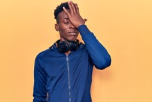 Young African American Man Wearing Sportswear And Headphones Surprised With Hand On Head For Mistake, Remember Error. Forgot, Bad Memory Concept.