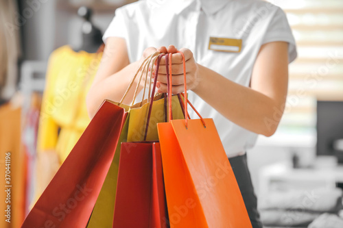 Obraz Female seller with shopping bags in modern clothes store - fototapety do salonu