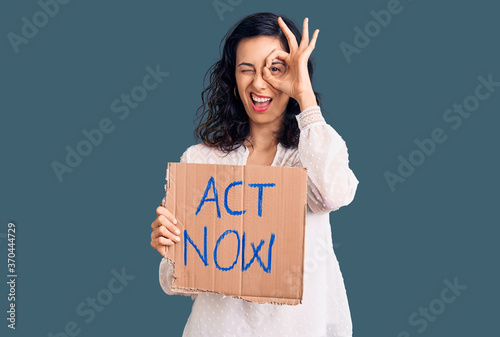 Young beautiful hispanic woman holding act now banner smiling happy doing ok sig Fototapet