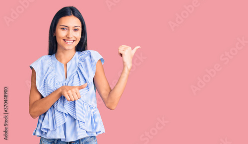 Young beautiful latin girl wearing casual clothes pointing to the back behind with hand and thumbs up, smiling confident
