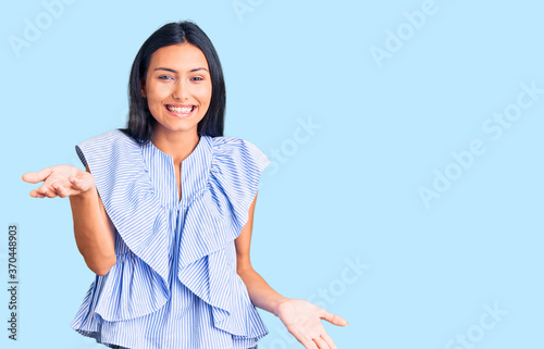 Young beautiful latin girl wearing casual clothes smiling cheerful with open arms as friendly welcome, positive and confident greetings