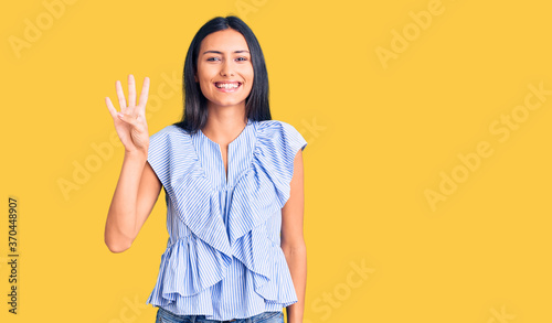 Young beautiful latin girl wearing casual clothes showing and pointing up with fingers number four while smiling confident and happy.