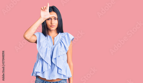 Young beautiful latin girl wearing casual clothes making fun of people with fingers on forehead doing loser gesture mocking and insulting.
