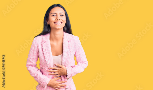 Young beautiful latin girl wearing business clothes smiling and laughing hard out loud because funny crazy joke with hands on body.