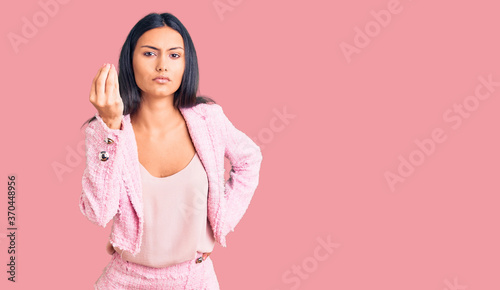Young beautiful latin girl wearing business clothes doing italian gesture with hand and fingers confident expression