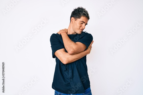 Young handsome man wearing casual clothes hugging oneself happy and positive, smiling confident. self love and self care
