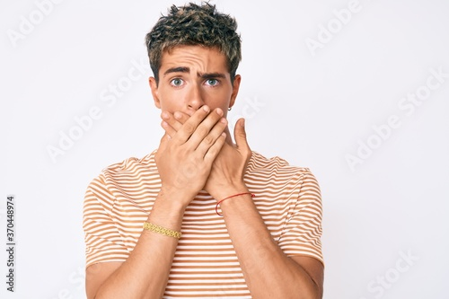 Young handsome man wearing casual clothes shocked covering mouth with hands for mistake. secret concept.