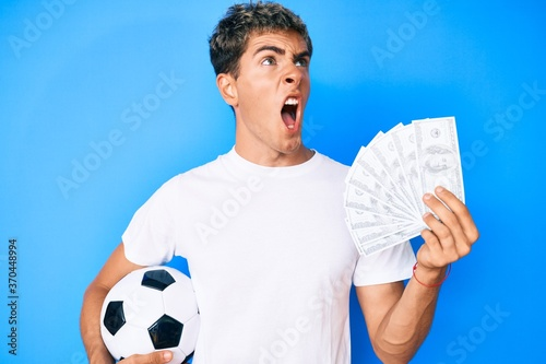 Young handsome man holding soccer ball and dollars banknotes angry and mad screaming frustrated and furious, shouting with anger. rage and aggressive concept.