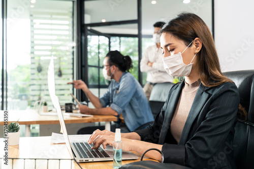 Asian young businesswoman wearing mask working on computer in office