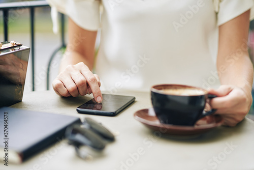 Fototapeta Close-up image of woman drinking cup of cappuccino and checking social media on