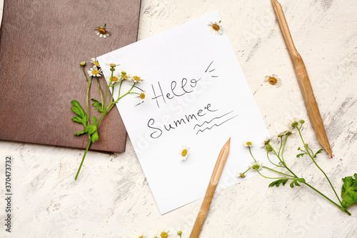 Paper sheet with text HELLO SUMMER and pens on white background