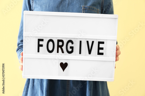 Obraz Woman holding board with word FORGIVE on color background, closeup - fototapety do salonu