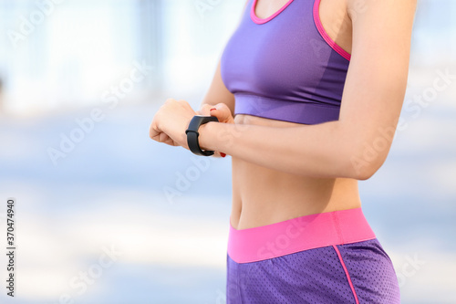 Obraz Sporty young woman with fitness tracker outdoors, closeup - fototapety do salonu