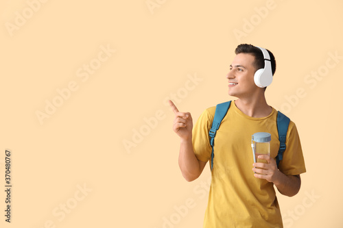 Obraz Young man with bottle of water and headphones pointing at something on color background - fototapety do salonu