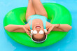 canvas print picture - Young woman listening to music in swimming pool