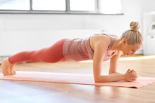 Fitness, Sport And Healthy Lifestyle Concept - Happy Smiling Young Woman Doing Yoga In Forearm Plank Pose At Home