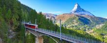 Zermatt, Switzerland. Gornergrat Red Tourist Train On The Bridge And Matterhorn Peak Banner Panorama In Swiss Alps