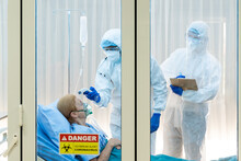 Medical Team In PPE Suit Treating Elderly Covid-19 Patient Wearing A Oxygen Mask In Restricted Areas. Caucasian Women Are Suffering From A Lung Infection. Part Of Coronavirus 2019-2020 Global Pandemic
