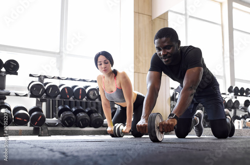 Fotografie, Tablou african man and caucasian woman doing exercises together in fitness gym, crossfit, gym, sport, training, workout exercises concept