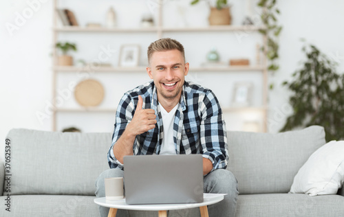 Happy handsome man sitting on couch showing thumb up
