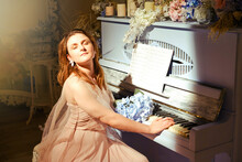 A Young Woman Plays An Old Piano In The Light. A Pianist Sits Next To A Vintage Musical Instrument With Flowers And Candles