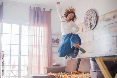 Cuadros en Lienzo Joyful lifestyle and success concept for female people - woman jumping on the co