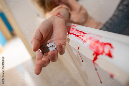 Fotomural A woman who has slit open her pulse veins with a razor blade in the bathroom