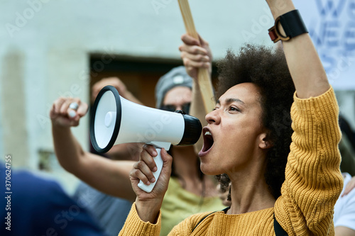 Fotografija African American woman with raised fist shouting through megaphone on anti-racism protest