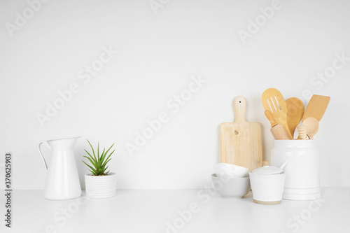 Obraz Kitchenware and utensils on a white shelf or countertop with a white wall background and copy space. Home kitchen cooking decor. - fototapety do salonu
