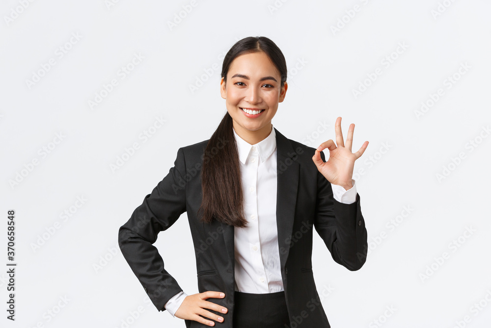 Fototapeta Professional female manager in black suit looking assertive, encourage everything okay, assure work done, showing okay gesture and smiling in approval, standing satisfied over white background
