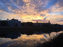 Reflective Pond By Apartment Buildings At Sunset