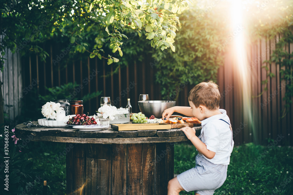 Fototapeta funny little boy in white shirt takes fresh blueberry from toast at table with festive setting in summerhouse green backyard.