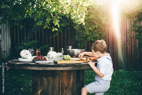 Obraz funny little boy in white shirt takes fresh blueberry from toast at table with festive setting in summerhouse green backyard. - fototapety do salonu