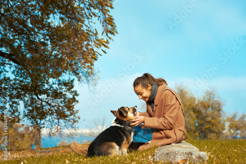 Autumn pet walking. woman in stylish coat sits with her Welsh Corgi dog in autumn park, looks at each other, eye contact with pet. Concept friendship with dog and human, autumn portrait