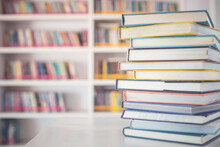 Book Stack On The Table In The Library Room And Blurred Space Of Bookshelf Background