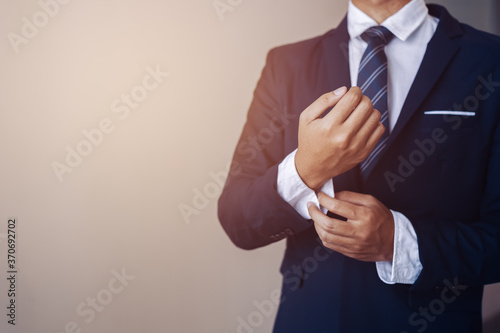 Fototapeta businessman wearing business suit fasten cufflink or button on sleeve of classic jacket and factory background