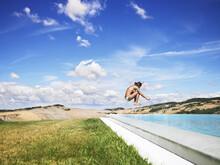 Woman Jumping In Swimming Pool...