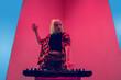 Leinwandbild Motiv Mood. Young female stylish, fashionable musician performing on blue-red background in neon light. Concept of music, hobby, festival, entertainment, emotions. Joyful party host, DJ, portrait of artist.