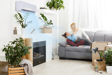 Air Conditioning In Living Room With Happy Family Moving To New Apartment