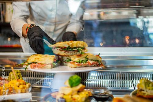 Banconista mentre sistema una focaccia con pomodori, mozzarella e rucola in vetr Tapéta, Fotótapéta