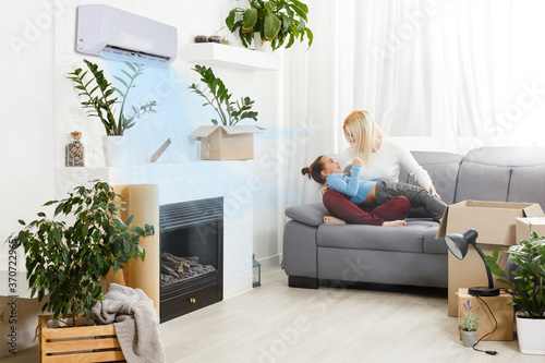 Fototapeta air conditioning in living room with happy family moving to new apartment obraz